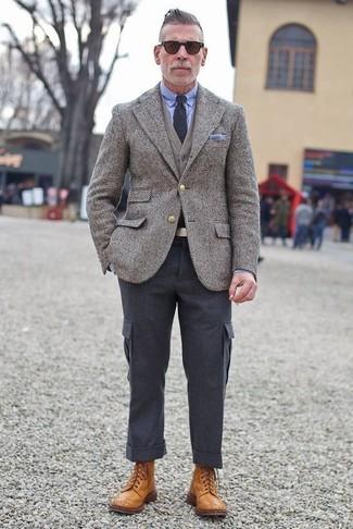 Combinar un pantalón cargo en gris oscuro: Para crear una apariencia para un almuerzo con amigos en el fin de semana ponte un blazer de lana de espiguilla gris y un pantalón cargo en gris oscuro. Haz botas brogue de cuero en tabaco tu calzado para mostrar tu inteligencia sartorial.