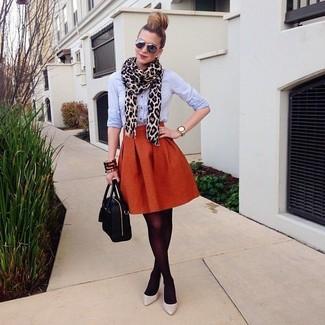 La versatilidad de una camisa de vestir celeste y una falda campana naranja los hace prendas en las que vale la pena invertir. Un par de zapatos de tacón de cuero grises se integra perfectamente con diversos looks.