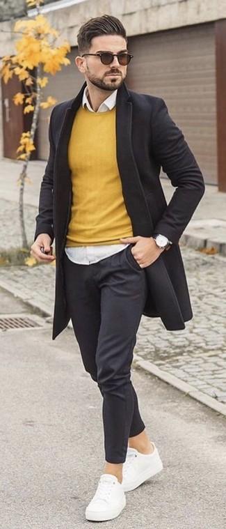 Cómo combinar: pantalón chino negro, camisa de vestir blanca, jersey con cuello circular amarillo, abrigo largo negro
