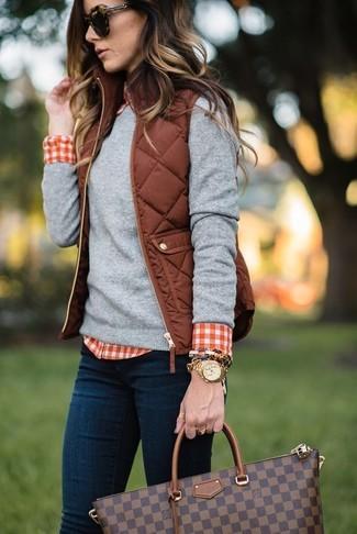 Cómo combinar: vaqueros pitillo azul marino, camisa de vestir de cuadro vichy en rojo y blanco, jersey con cuello circular gris, chaqueta sin mangas acolchada marrón