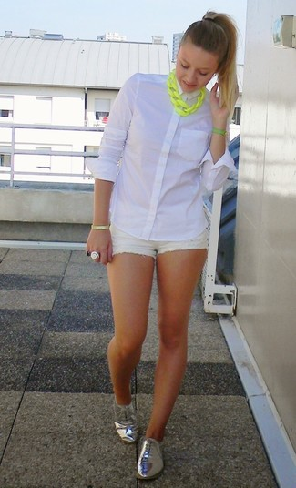 Los días ocupados exigen un atuendo simple aunque elegante, como una camisa de vestir blanca y unos pantalones cortos blancos. Completa el look con zapatos oxford de cuero plateados.