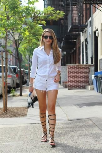 Cómo combinar: camisa de vestir blanca, pantalones cortos vaqueros blancos, sandalias romanas altas de cuero negras, cartera sobre de cuero сon flecos blanca