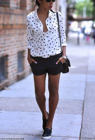 Una camisa de vestir a lunares en blanco y negro y unos pantalones cortos negros son prendas que debes tener en tu armario. Para el calzado ve por el camino informal con zapatillas slip-on de cuero negras.