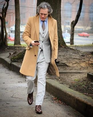 Cómo combinar: zapatos derby de cuero en marrón oscuro, camisa de vestir celeste, traje de tres piezas gris, abrigo largo marrón claro