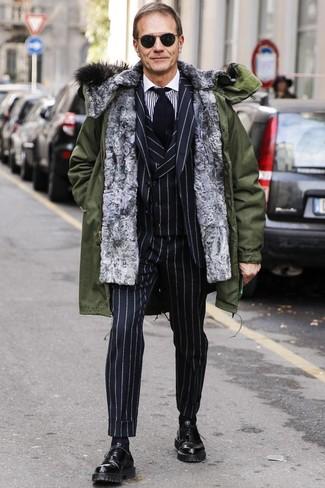 Cómo combinar: zapatos oxford de cuero negros, camisa de vestir de rayas verticales en blanco y negro, traje de tres piezas de rayas verticales negro, parka verde oliva