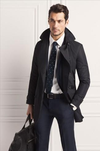Cómo combinar: bolsa de viaje de cuero negra, camisa de vestir blanca, traje a cuadros azul marino, gabardina negra