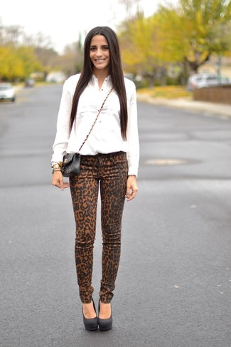 Cómo combinar: camisa de vestir blanca, vaqueros pitillo de leopardo marrón claro, zapatos de tacón de ante negros, bolso bandolera de cuero acolchado negro
