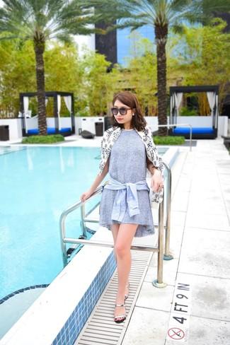 Cómo combinar: sandalias planas de cuero plateadas, camisa de vestir celeste, vestido amplio gris, chubasquero estampado en blanco y negro