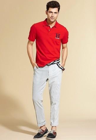 Cómo combinar: camisa polo roja, pantalón chino blanco, náuticos de lona negros, correa de lona de rayas horizontales en negro y blanco