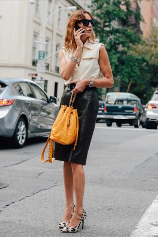 Los días ocupados exigen un atuendo simple aunque elegante, como una camisa sin mangas en beige y una falda lápiz de cuero negra. Complementa tu atuendo con zapatos de tacón de ante de leopardo blancos.