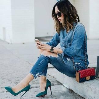 Cómo combinar: camisa vaquera azul, vaqueros pitillo desgastados azules, zapatos de tacón de ante en verde azulado, bolso bandolera de cuero acolchado rojo