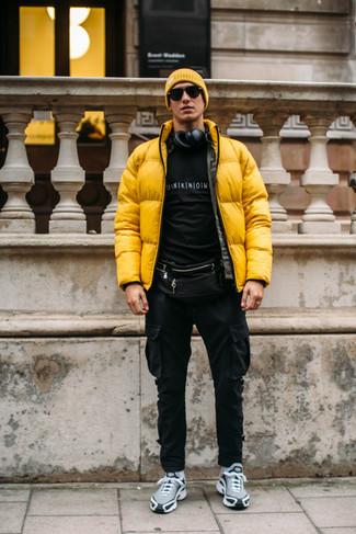 Outfits hombres: Para crear una apariencia para un almuerzo con amigos en el fin de semana utiliza un plumífero amarillo y un pantalón cargo negro. Haz este look más informal con deportivas grises.