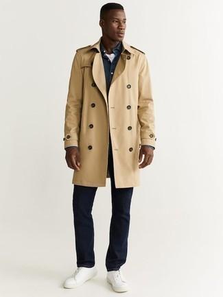 Outfits hombres: Utiliza una gabardina marrón claro y unos vaqueros azul marino para lograr un look de vestir pero no muy formal. ¿Quieres elegir un zapato informal? Elige un par de tenis de cuero blancos para el día.