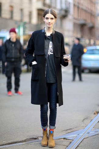 Cómo combinar: vaqueros pitillo azul marino, camiseta con cuello circular estampada en negro y blanco, chaqueta motera de cuero negra, abrigo negro