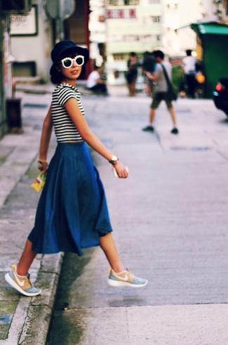 Emparejar una camiseta con cuello circular y una falda midi vaquera azul marino es una opción cómoda para hacer diligencias en la ciudad. Si no quieres vestir totalmente formal, elige un par de tenis celestes.
