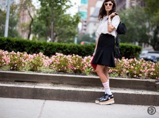 Cómo combinar: camiseta con cuello circular blanca, falda skater negra, mocasín con plataforma de cuero de estrellas en negro y blanco, mochila con cordón de ante negra