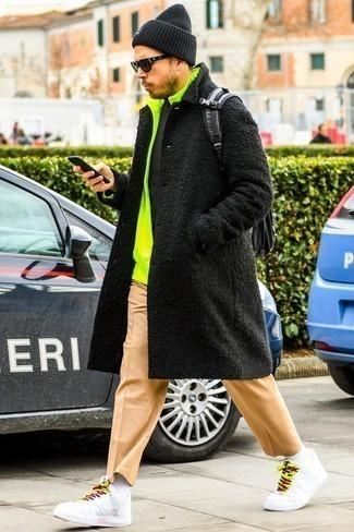 Combinar un abrigo largo negro: Ponte un abrigo largo negro y un pantalón chino marrón claro para lograr un look de vestir pero no muy formal. Mezcle diferentes estilos con tenis de cuero blancos.