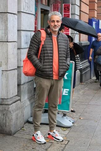 Cómo combinar: pantalón de chándal verde oliva, camiseta con cuello circular gris, jersey con cuello circular naranja, plumífero en gris oscuro