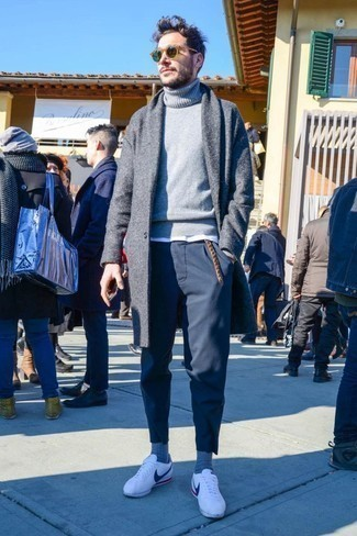 Combinar un abrigo largo gris: Empareja un abrigo largo gris con un pantalón chino azul marino para lograr un look de vestir pero no muy formal. Mezcle diferentes estilos con tenis de cuero blancos.