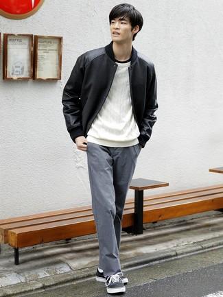 Cómo combinar: pantalón chino gris, camiseta con cuello circular negra, jersey de ochos blanco, chaqueta varsity negra