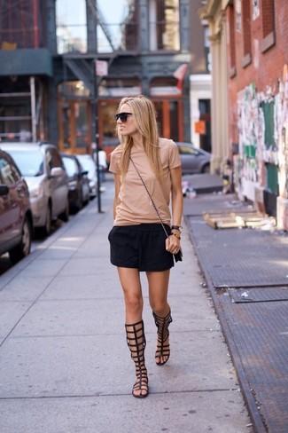 Cómo combinar: camiseta con cuello circular en beige, minifalda negra, sandalias romanas altas de cuero negras, bolso bandolera de cuero negro