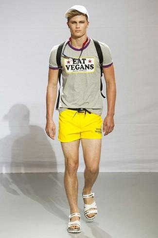 Cómo combinar: camiseta con cuello circular estampada gris, pantalones cortos amarillos, sandalias de cuero blancas, mochila de lona negra