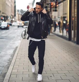 Cómo combinar: vaqueros pitillo negros, camiseta con cuello circular blanca, sudadera con capucha negra, chaqueta motera de cuero negra