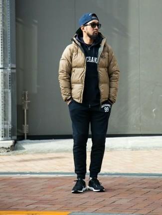 Cómo combinar: pantalón de chándal negro, camiseta con cuello circular negra, sudadera con capucha estampada en negro y blanco, plumífero marrón claro