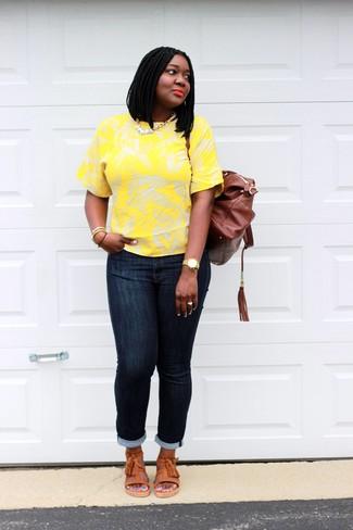 Cómo combinar: camiseta con cuello circular con print de flores amarilla, vaqueros pitillo azul marino, sandalias planas de cuero naranjas, mochila de cuero marrón