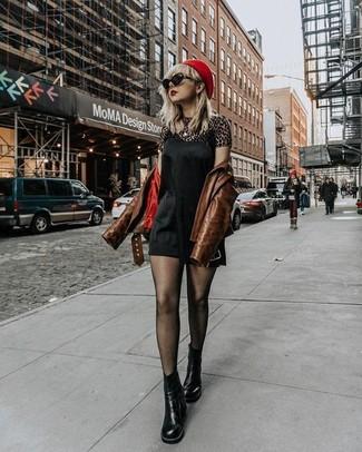 Cómo combinar: botines chelsea de cuero negros, camiseta con cuello circular de leopardo marrón, vestido camisola de seda negro, chaqueta motera de cuero marrón