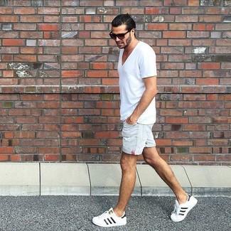 Cómo combinar: camiseta con cuello en v blanca, pantalones cortos vaqueros blancos, tenis blancos, gafas de sol en marrón oscuro