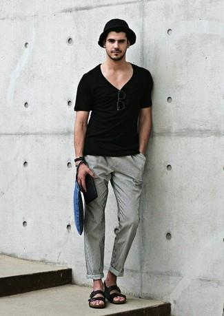 Cómo combinar: camiseta con cuello en v negra, pantalón chino gris, sandalias de cuero negras, sombrero de paja negro