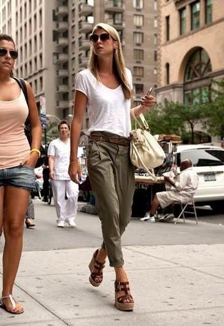Cómo combinar: camiseta con cuello en v blanca, pantalón chino verde oliva, sandalias con cuña de cuero en marrón oscuro, bolsa tote de cuero en beige