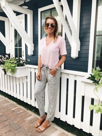Cómo combinar: camiseta con cuello en v de rayas horizontales rosada, pantalón de chándal gris, sandalias planas de cuero marrón claro, gafas de sol en marrón oscuro