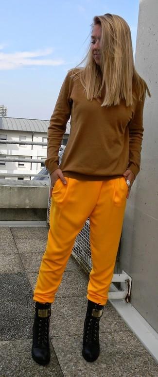 Emparejar una camiseta de manga larga tabaco y unos pantalones de pijama amarillos es una opción cómoda para hacer diligencias en la ciudad. Dale un toque de elegancia a tu atuendo con un par de botines de cuero negros.