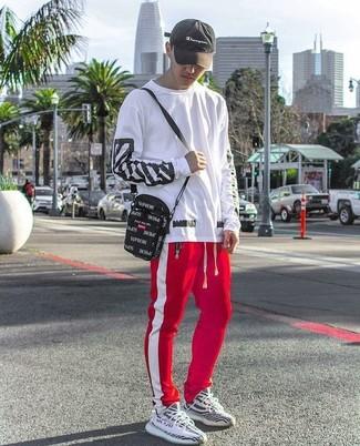 Cómo combinar: camiseta de manga larga en blanco y negro, pantalón de chándal de rayas verticales en rojo y blanco, deportivas en negro y blanco, bolso mensajero de lona negro