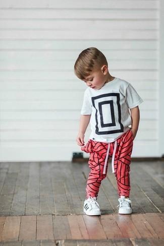 Cómo combinar: camiseta estampada en blanco y negro, pantalón de chándal rojo, zapatillas blancas
