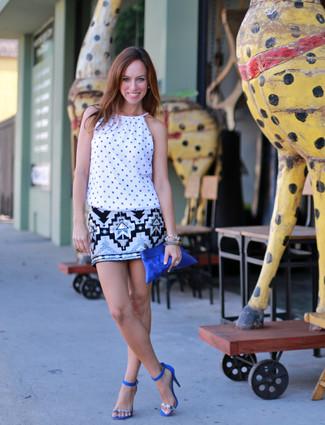 Cómo combinar: camiseta sin manga a lunares blanca, minifalda de lentejuelas con estampado geométrico blanca, sandalias de tacón de ante azules, cartera sobre de ante azul