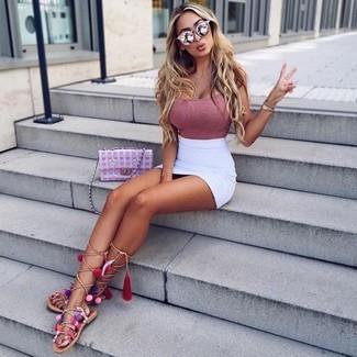 Cómo combinar: camiseta sin manga rosada, minifalda blanca, sandalias romanas altas de cuero en beige, bolso bandolera de cuero acolchado rosado