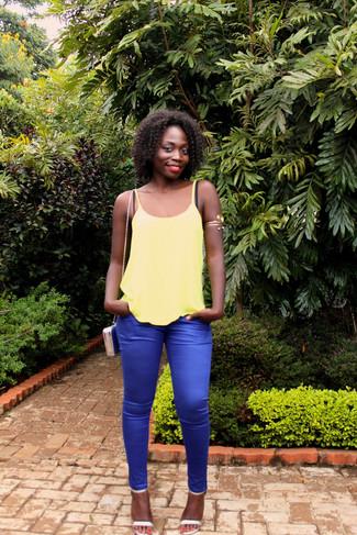 Cómo combinar: camiseta sin manga amarilla, pantalones pitillo azules, sandalias de tacón de cuero plateadas, bolso bandolera de cuero azul