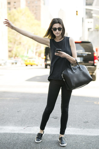 Este combinación de una camiseta sin manga negra y unos vaqueros pitillo negros te da una onda muy informal y accesible. Zapatillas slip-on de cuero negras son una sencilla forma de complementar tu atuendo.