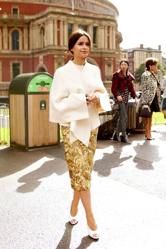 Cómo combinar: capa en beige, jersey con cuello circular en beige, falda lápiz de lentejuelas dorada, zapatos de tacón de cuero con recorte blancos
