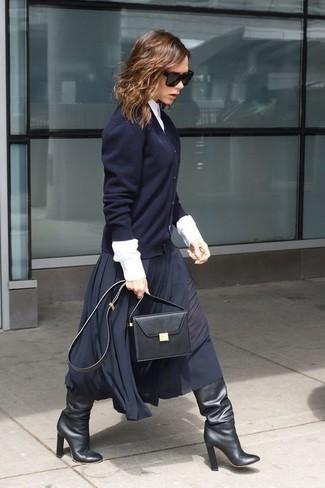Look de Victoria Beckham: Cárdigan azul marino, Camisa de vestir blanca, Falda midi plisada azul marino, Botas de caña alta de cuero negras