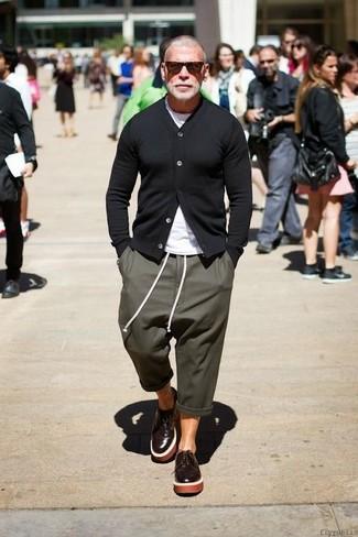 Look de Nick Wooster: Cárdigan Negro, Camiseta con Cuello Circular Blanca, Pantalón de Chándal Verde Oliva, Zapatos Derby de Cuero en Marrón Oscuro