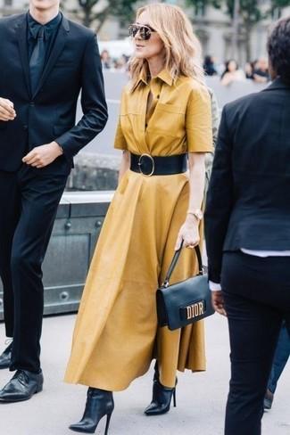 Cómo combinar: cinturón de cuero negro, cartera sobre de cuero negra, botines de cuero negros, vestido camisa mostaza