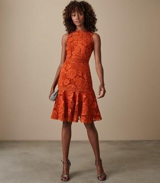 Cómo combinar: cartera sobre con adornos plateada, sandalias de tacón de cuero plateadas, vestido de vuelo de encaje naranja