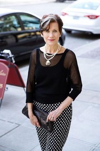 Moda para mujeres de 60 años: Emparejar un jersey de manga corta negro y un pantalón de pinzas a lunares en negro y blanco es una opción cómoda para hacer diligencias en la ciudad.