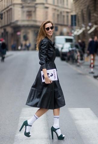 Cómo combinar: calcetines blancos, cartera sobre estampada en blanco y negro, sandalias de tacón de ante verde oscuro, vestido camisa de cuero negra