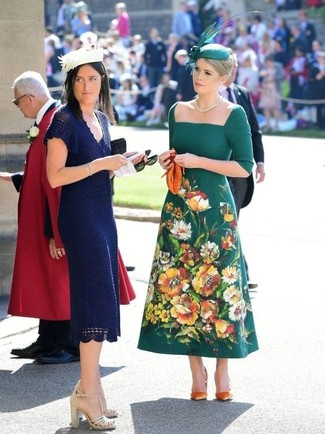 Cómo combinar: sombrero con adornos verde, cartera sobre de cuero naranja, zapatos de tacón de ante naranjas, vestido midi bordado verde oscuro