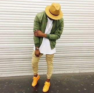 Cómo combinar: cazadora de aviador verde oliva, camiseta con cuello circular blanca, pantalón de chándal marrón claro, tenis amarillos